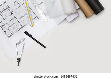 Top view workspace mockup of architectural project with laptop computer, architectural project plan, engineering tools and office supplies on white desk empty space for your text isolated on white