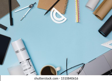 Top view workspace mockup of architectural project with laptop computer, architectural project plan, engineering tools, office supplies and hot coffee cup on blue desk empty space isolated on blue