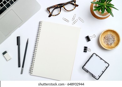 Top view workspace mockup on white background  with notebook, pen, glasses, clips and accessories.