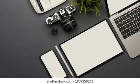Top view of workspace with smartphone, tablet, laptop, camera and plant pot on the table, clipping path
