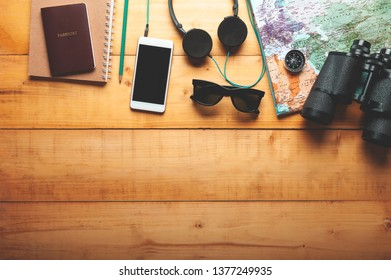 Top view of world map, headphone, binocular, smartphone and passport with texting space on wooden background, vacation or travelling concept, plan a trip, Itinerary planner.