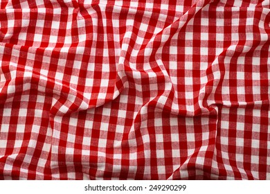 Top view wrinkled tablecloth red tartan in a cage texture wallpaper horizontal. Unique perspectives.