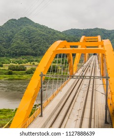 Top view of yellow arched truss railroad bridge spanning a river in the countryside on cloudy day.