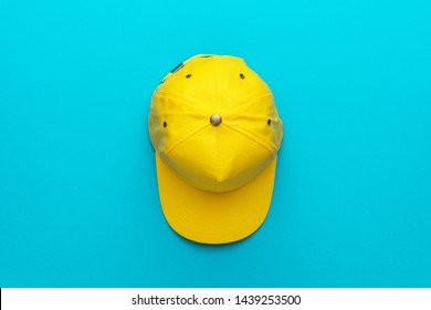 Top view of the yellow baseball cap on turquoise blue background. Flat lay image of baseball cap with central composition. Photo of unisex bright headwear with copy space.