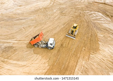 top view of yellow bulldozer and dump truck working at road construction site