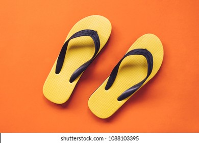 Top view of Yellow flipflop on orange background