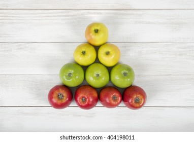 Top view of yellow, green and red apples creating a triangle shape
