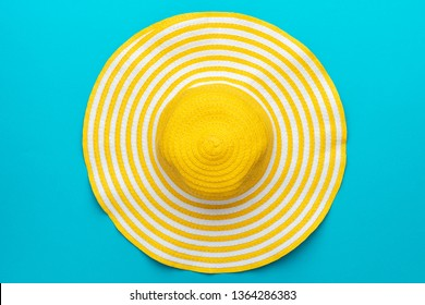 top view of yellow hat close-up over blue background. minimalist photo of striped retro hat summer concept