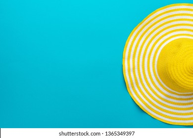 top view of yellow hat close-up over blue background. minimalist photo of striped retro hat with copy space