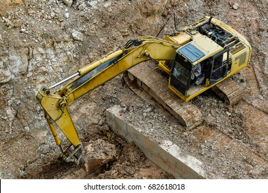 Top view Yellow industrial backhoe tracktor working at the construction site.