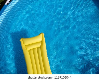 Top view of a yellow inflatable mattress in an above ground private backyard swimming pool