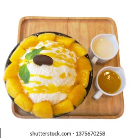 Top view of yellow mango ice shaved bing su with chocolate cookie place at the top decorated with yellowish mango and sweet milk served on the wooden plate on the white background. known as  kakigori