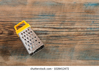 top view yellow metal grater on wooden table with space for food or text