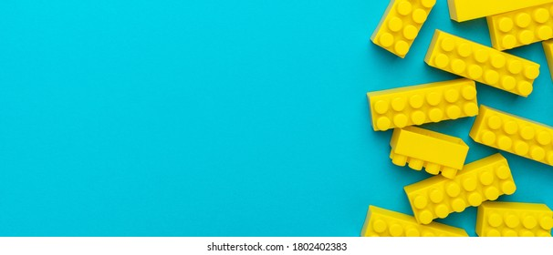 Top view of yellow plastic blocks. Right side composition of yellow building blocks from child constructor. Bright plastic blocks on turquoise blue background with copy space.