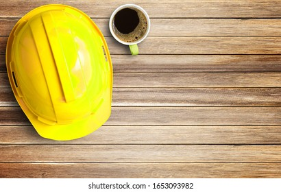 Top view yellow safety helmet and cup of coffee on wood table background in office workplace. Copy space for any design.