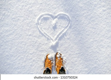 Top view of yellow shoes / boots footprint in fresh snow. Winter season. Looking at the drawn heart in the snow. Valentines day.