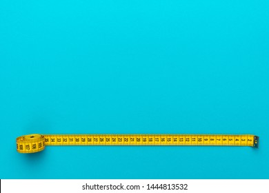 Top view of yellow soft measuring tape. Minimalist flat lay image of tape measure with metric scale over turquoise blue background with copy space. Photo of body measuring tape as diet concept.