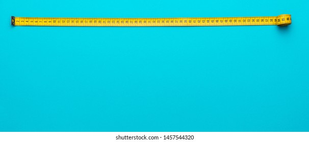Top view of yellow soft measuring tape. Minimalist flat lay image of tape measure with metric scale over turquoise blue background with copy space.