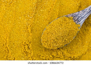 Top view of yellow spicy Curry Powder in wooden spoon, main ingredient seasoning to cook Asian curry on blurred spice background
