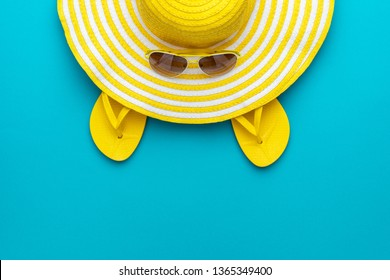 top view of yellow sunglasses, striped retro hat and flip-flops summer concept. flat lay minimalist photo of yellow beach accessories on the turquoise blue background with copy space