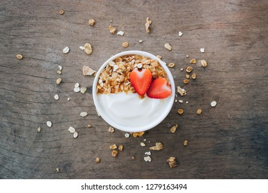 Top view of yogurt in a wooden bowl with granola,fresh strawberry on white wooden table. Health food concept.