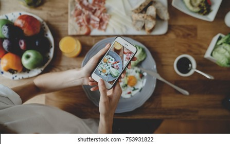 Top view of youn hipster girl taking photo of food via her smartphone, blogger woman taking photo of breakfast on her mobile