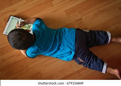 Top View Of A Young Asian Boy Lying On The Wooden Floor Engross In Playing  With