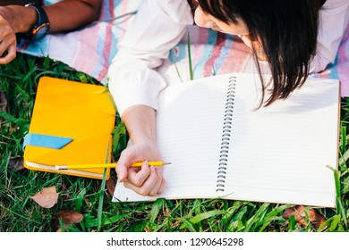 Top view of young Asian female student going to write and draw on empty blank paper of notebook in nature green park - with copy space
