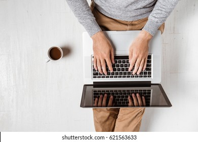 Top view of young asian man sitting on floor with laptop