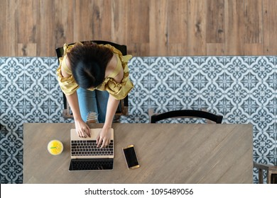 Top view of young asian woman sitting, using laptop in modern workplace, café coffee shop. Urban female college lifestyle concept on wooden table, blue vintage floor tile pattern with copy space.