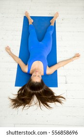 Top view of a young attractive woman practicing yoga, lying in Dead Body, Corpse exercise, Savasana pose, working out wearing sportswear, blue suit, indoor full length, white loft studio background