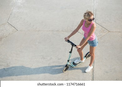 top view Young beautiful girl poising in summer in city and next to blue kick scooter
