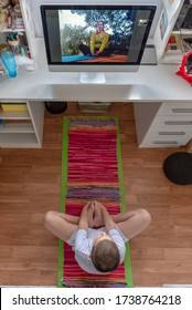 Top view of a young boy on mat doing yoga, having online yoga class on computer in his room, during pandemic, social distancing and isolation