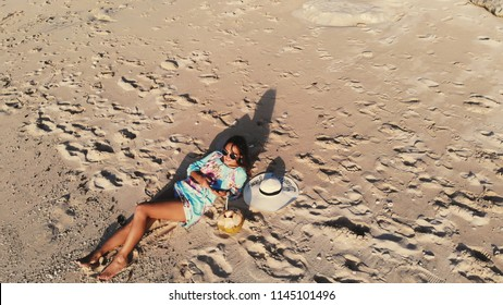 Top view of young brunette woman in sunglasses lying on tropical paradise beach and uses mobile phone during beautiful sunset. Travel concept