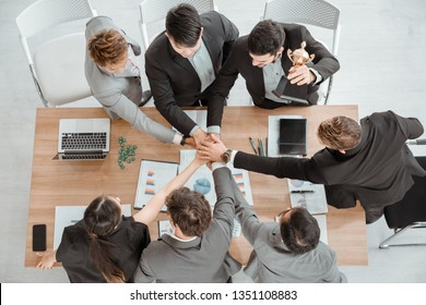 top view of young business people putting their hands together. Stack of hands and show trophy. Unity and teamwork concept.