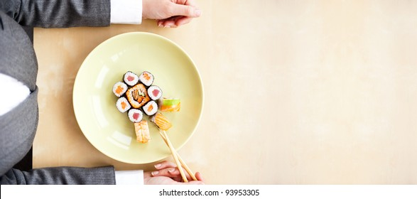 Top view of young business woman wearing suit holding sushi sticks in her arms. Sushi rolls set on plate. Business lunch offer concept