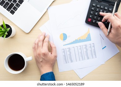 Top view of young businessman analyzing on business graphs documents and using calculator over white office desk table with laptop computer. Business and economy concept.