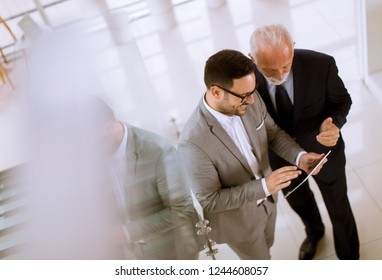 Top view  of young businessman pointing and showing something to senior partner on digital tablet at office