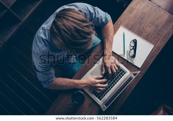 Vista superior del joven trabajador ocupado escribiendo en el portátil