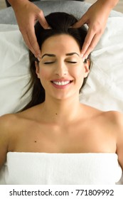 Top view of young caucasian smiling woman receiving a head massage in a spa center with eyes closed. Female patient is receiving treatment by professional therapist.