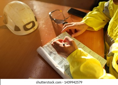 Top view of young construction gold miner worker hand holding pen writing job hazards analysis on working at height risk assessment safety control permit prior to start morning shift during shut down