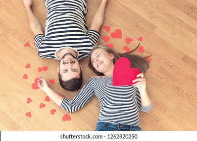 Top view young couple lying on the floor and looking to camera and smile.