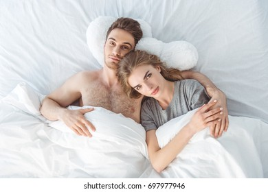 top view of young couple lying in bed at morning