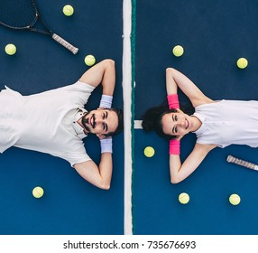 Top view of young couple is lying on tennis court. Handsome man and attractive woman are playing tennis.