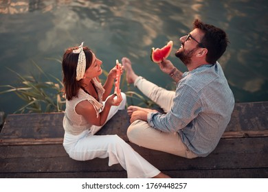 top view of young couple sitting  by the river,  eating watermelon