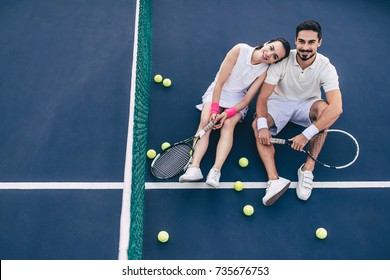 Top view of young couple is sitting on tennis court. Handsome man and attractive woman are playing tennis.
