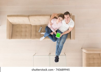 top view of Young couple sitting on a sofa in the luxury living room, using a tablet computer