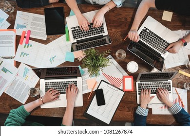 Top view of young coworking people are working on laptops and paper documents. Group of college students using laptop while sitting around table. Team of hipsters making new great startup. Concept