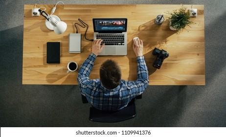 Top View of Young Creative Man Working on His Laptop Beside Him on the Table Lies Notebook and Headphones.