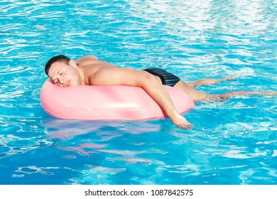top view of young drunk guy swim with pink circle in pool. drunk guy on vacation in the hotel.